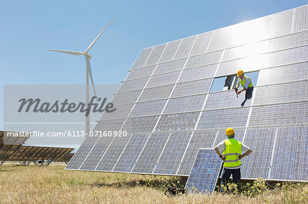Workers examining solar panel in rural landscape Stock Photo - Premium Royalty-Free, Image code: 6113-07160920