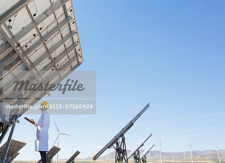 Scientist examining solar panel in rural landscape Stock Photo - Premium Royalty-Free, Image code: 6113-07160924