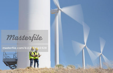 Workers talking by wind turbines in rural landscape Stock Photo - Premium Royalty-Free, Image code: 6113-07160928