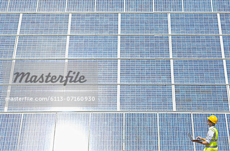 Worker examining solar panel in rural landscape Stock Photo - Premium Royalty-Free, Image code: 6113-07160930