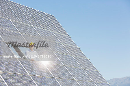 Worker examining solar panel in rural landscape Stock Photo - Premium Royalty-Free, Image code: 6113-07160934
