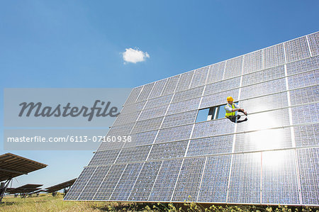 Worker examining solar panel in rural landscape Stock Photo - Premium Royalty-Free, Image code: 6113-07160938