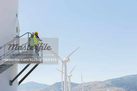 Workers standing on wind turbine in rural landscape Stock Photo - Premium Royalty-Free, Image code: 6113-07160939