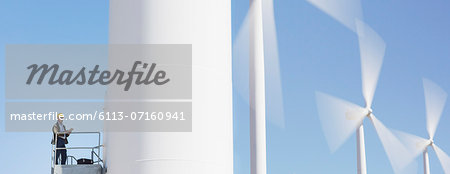 Worker standing on wind turbine in rural landscape Stock Photo - Premium Royalty-Free, Image code: 6113-07160941