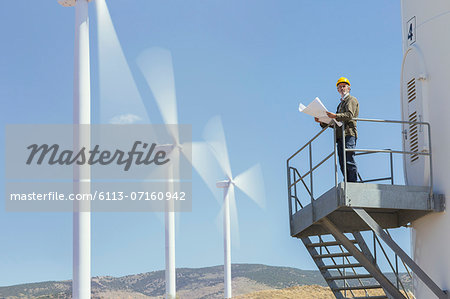 Worker standing on wind turbine in rural landscape Stock Photo - Premium Royalty-Free, Image code: 6113-07160942