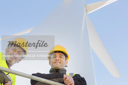 Workers standing on wind turbine in rural landscape Stock Photo - Premium Royalty-Free, Image code: 6113-07160943