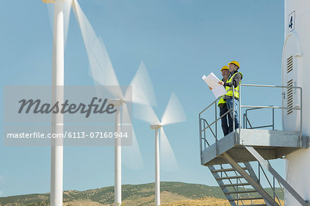 Workers standing on wind turbine in rural landscape Stock Photo - Premium Royalty-Free, Image code: 6113-07160944