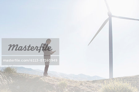 Businessman using laptop by wind turbine in rural landscape Stock Photo - Premium Royalty-Free, Image code: 6113-07160949
