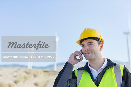 Worker using walkie talkie in rural landscape Stock Photo - Premium Royalty-Free, Image code: 6113-07160953
