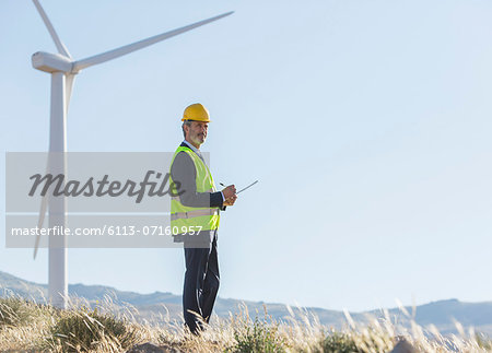 Businessman examining wind turbines in rural landscape Stock Photo - Premium Royalty-Free, Image code: 6113-07160957