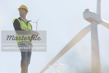 Worker by wind turbines in rural landscape Stock Photo - Premium Royalty-Free, Image code: 6113-07160963
