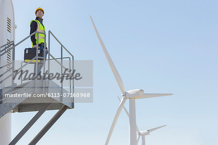 Worker standing on wind turbine in rural landscape Stock Photo - Premium Royalty-Free, Image code: 6113-07160968