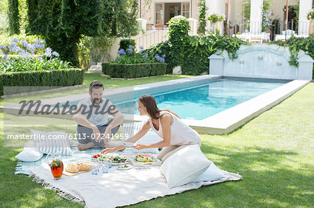 Couple enjoying picnic by pool Stock Photo - Premium Royalty-Free, Image code: 6113-07241959