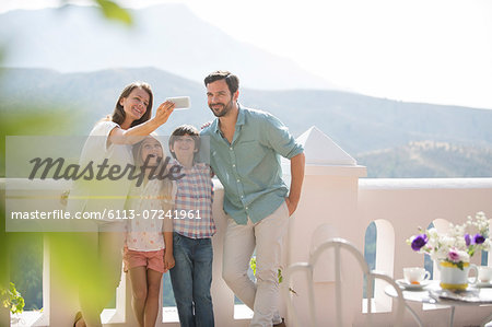 Family taking self-portrait on sunny balcony Stock Photo - Premium Royalty-Free, Image code: 6113-07241961