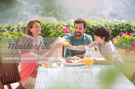 Family toasting orange juice glasses at table in garden