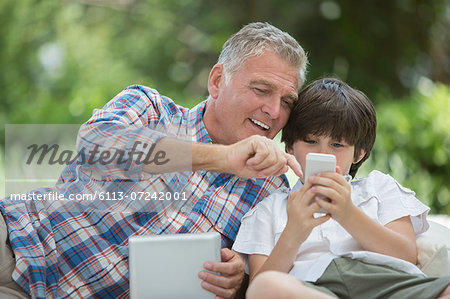 Grandfather and grandson using digital tablet and cell phone Stock Photo - Premium Royalty-Free, Image code: 6113-07242001