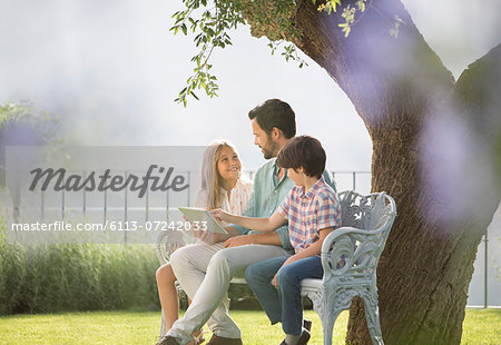 Father and children using digital tablet on bench in park Stock Photo - Premium Royalty-Free, Image code: 6113-07242033