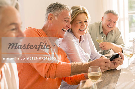 Senior couples drinking wine and looking at cell phone Stock Photo - Premium Royalty-Free, Image code: 6113-07242055