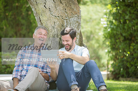 Father and son using digital tablet outdoors Stock Photo - Premium Royalty-Free, Image code: 6113-07242061
