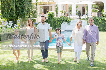 Multi-generation family holding hands and walking in backyard Stock Photo - Premium Royalty-Free, Image code: 6113-07242063