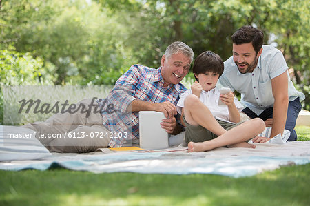 Multi-generation men with cell phone on blanket in grass Stock Photo - Premium Royalty-Free, Image code: 6113-07242103