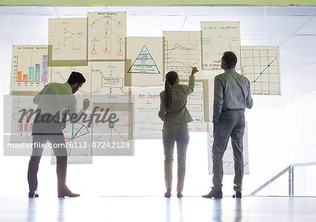 Business people working with charts and graphs on glass wall Stock Photo - Premium Royalty-Free, Image code: 6113-07242128