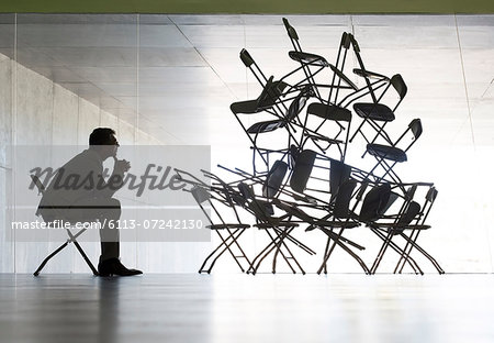 Businessman viewing office chair installation art Stock Photo - Premium Royalty-Free, Image code: 6113-07242130