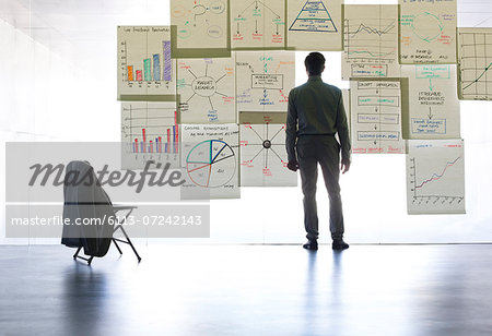 Businessman looking at graphs and charts on glass wall in office Stock Photo - Premium Royalty-Free, Image code: 6113-07242143