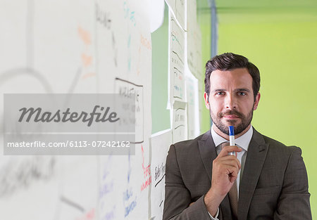 Businessman thinking at glass wall Stock Photo - Premium Royalty-Free, Image code: 6113-07242162
