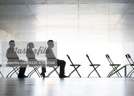 Business people sitting in office chairs in a row Stock Photo - Premium Royalty-Free, Image code: 6113-07242166