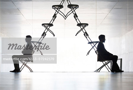 Businessmen sitting at opposite ends of office chair installation art Stock Photo - Premium Royalty-Free, Image code: 6113-07242170