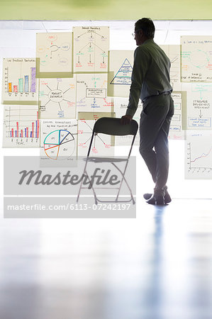 Businessman viewing charts and graphs on office wall Stock Photo - Premium Royalty-Free, Image code: 6113-07242197