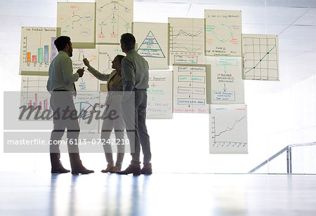 Business people discussing charts and graphs hanging in office Stock Photo - Premium Royalty-Free, Image code: 6113-07242210