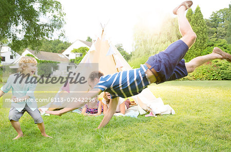 Family playing outside teepee in backyard Stock Photo - Premium Royalty-Free, Image code: 6113-07242296