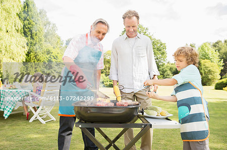 Men grilling meat on barbecue in backyard Stock Photo - Premium Royalty-Free, Image code: 6113-07242299