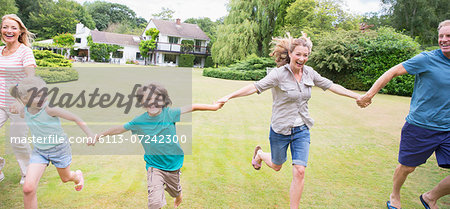 Multi-generation family holding hands and running in backyard Stock Photo - Premium Royalty-Free, Image code: 6113-07242300