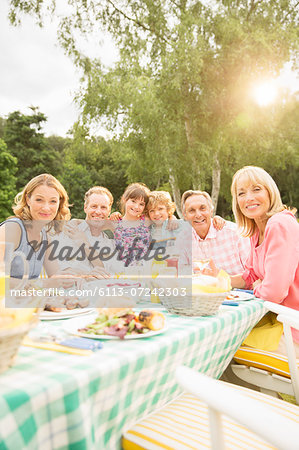 Multi-generation family eating lunch at table in backyard