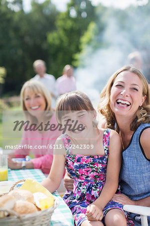 Mother and daughter laughing at table in backyard Stock Photo - Premium Royalty-Free, Image code: 6113-07242309