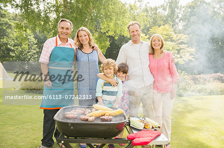 Multi-generation family standing at barbecue in backyard Stock Photo - Premium Royalty-Free, Image code: 6113-07242313