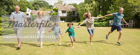 Multi-generation family holding hands and running in grass Stock Photo - Premium Royalty-Free, Image code: 6113-07242333