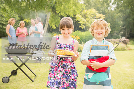 Brother and sister holding grilled corn near barbecue in backyard Stock Photo - Premium Royalty-Free, Image code: 6113-07242362