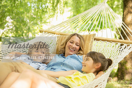 Mother and children relaxing together in hammock
