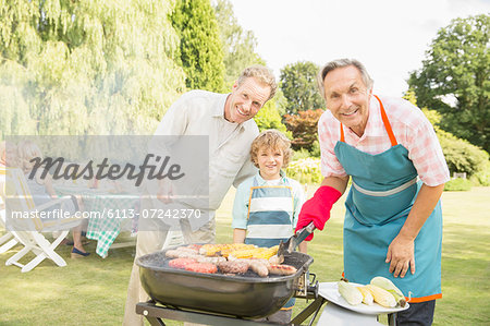 Multi-generation men grilling meat and corn at barbecue in backyard Stock Photo - Premium Royalty-Free, Image code: 6113-07242370