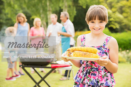 Smiling girl holding grilled corn in backyard Stock Photo - Premium Royalty-Free, Image code: 6113-07242374
