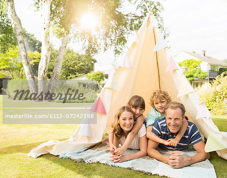 Family relaxing in teepee in backyard Stock Photo - Premium Royalty-Free, Image code: 6113-07242388