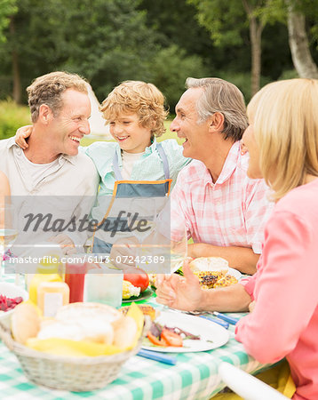 Family enjoying lunch at table in backyard