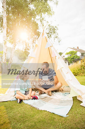 Father and son using digital tablet in teepee in backyard Stock Photo - Premium Royalty-Free, Image code: 6113-07242392