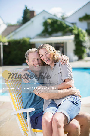 Couple sitting in lounge chair at poolside Stock Photo - Premium Royalty-Free, Image code: 6113-07242393