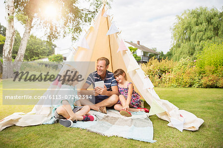 Father and children relaxing in teepee in backyard Stock Photo - Premium Royalty-Free, Image code: 6113-07242394