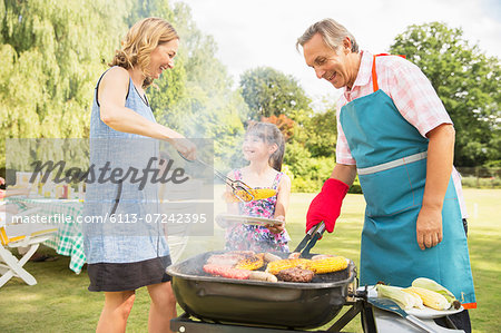 Multi-generation family standing at barbecue in backyard Stock Photo - Premium Royalty-Free, Image code: 6113-07242395